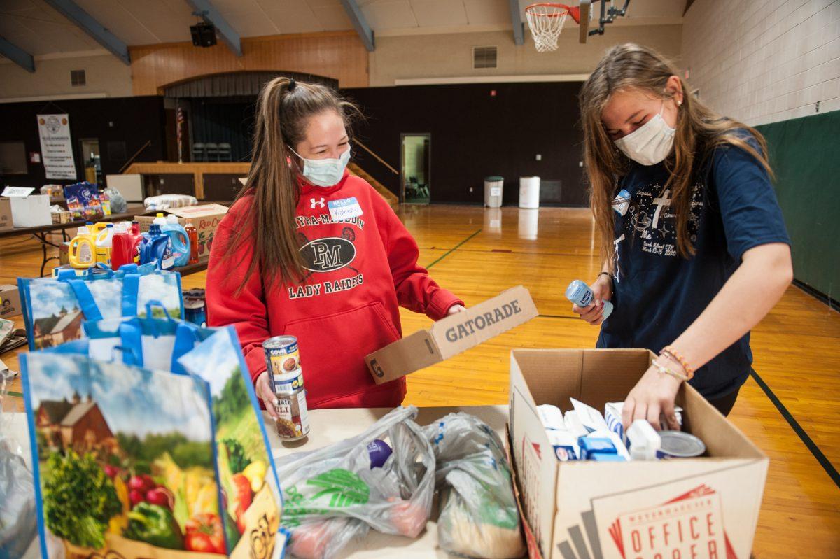 Kaleen Anderson (izquierda) y Brigid Lang organizan donaciones en la iglesia de San Juan de Rochester durante la campaña de alimentos y suministros el 13 de junio.