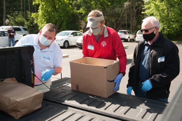 Brian Thomas (desde la izquierda) John Bednarczyk y Ed Buckley descargan donaciones.