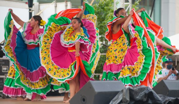 Women dance in colorful dresses.