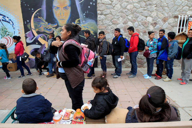 Central American migrants who were dropped off at a bus station in El Paso, Texas, line up for food Dec. 25 as they wait for transportation to emergency shelters.