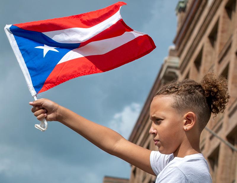 Boy waves a Puerto Rican flag.