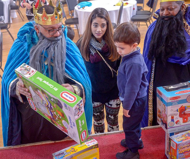 Cristal Santiago (centro) observa mientras Ray Mayoliz, retratando uno de los Tres Reyes Magos, presenta un regalo a Jovani Ortiz.