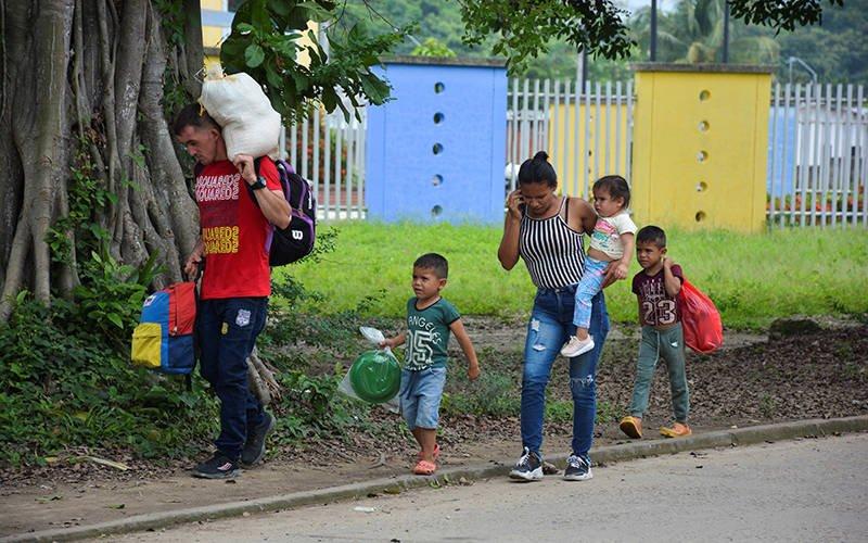 Refugiados venezolanos caminan por una calle en Arauquita, Colombia, el 5 de abril de 2021 tras huir de su país debido a una ofensiva militar. Grupos de iglesias en Colombia se están movilizando para apoyar a miles de refugiados venezolanos que recientemente huyeron de una ofensiva militar y ahora están atrapados en la remota ciudad fronteriza colombiana.