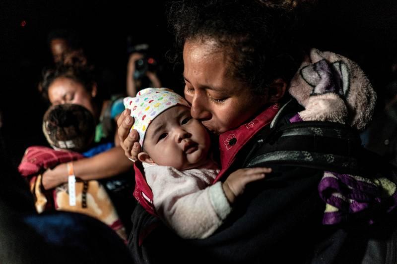 Una madre de Guatemala que busca asilo en los EE. UU. besa a su bebé de tres meses mientras espera ser escoltada por agentes de la Patrulla Fronteriza en Roma, Texas, el 7 de abril de 2021, luego de cruzar el Río Bravo hacia los Estados Unidos