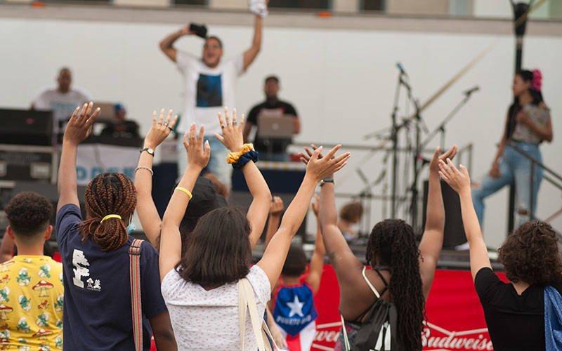 CUTLINE: Los asistentes al festival levantan la mano en un intento por atrapar los productos que se arrojan a la multitud entre actos musicales el 21 de agosto en el Festival Puertorriqueño de Rochester.