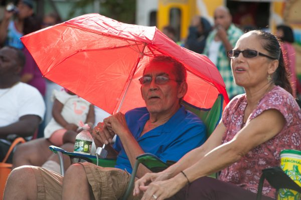A man sits underneath a red umbrella.