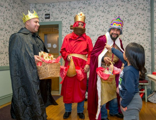 Men dressed as kings hand out gifts.