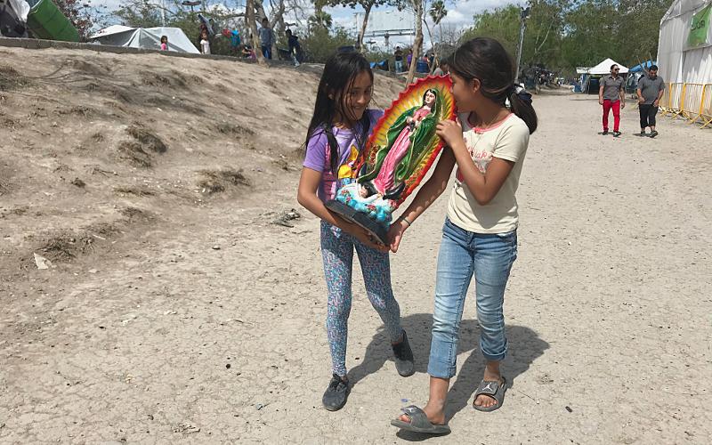 Dos niñas llevan una estatua