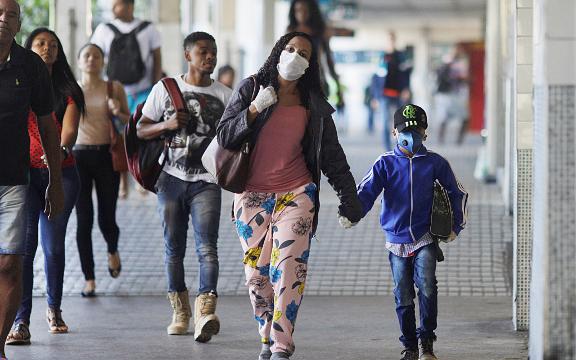 Una mujer y un niño con máscaras protectoras caminan