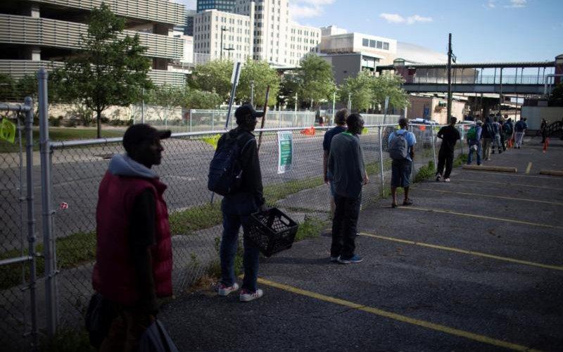 """Un grupo de personas en Nueva Orleans practica el distanciamiento social mientras espera una comida el 31 de marzo de 2020, durante la pandemia de coronavirus. Los Centros para el Control y Prevención de Enfermedades, dijeron en un reciente comunicado que cierta información sugiere """"que personas en grupos minoritarios étnicos y raciales están desproporcionadamente contagiando y muriendo"""", de COVID-19, en particular latinos y afroamericanos."""