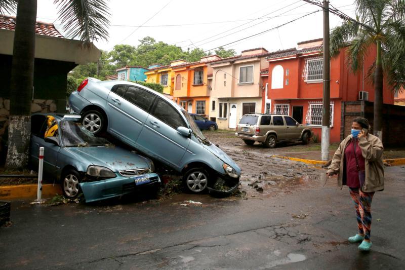 Una mujer con una mascarilla protectora pasa frente a un grupo de autos dañados en San Salvador, El Salvador, el 31 de mayo de 2020, después de que la tormenta tropical Amanda afectara el área. Centroamérica, batallando COVID, ahora enfrenta efectos de tormentas tropicales causando destrucción en la región. (Foto CNS por José Cabezas/Reuters)