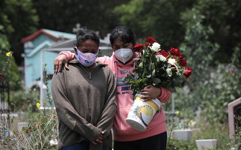 Familiares con m·scaras protectoras se acercan al ata˙d de un hombre durante su entierro en un cementerio en la Ciudad de MÈxico el 6 de agosto de 2020, durante la pandemia de COVID-19.