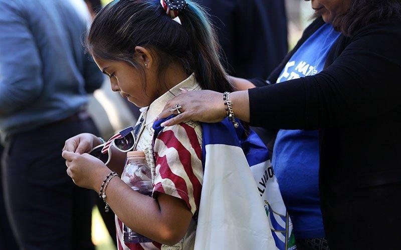 Marilyn Miranda, de 9 años, cubierta con una bandera salvadoreña, y junto a su madre, estuvo presente en una manifestación apoyando la inmigración frente al Capitolio de los EE. UU. en Washington, el 4 de junio de 2019. Hasta el 14 de septiembre de 2020, la decisión de la Corte de Apelaciones del Noveno Circuito de los EE. UU. en Ramos v. Nielsen acerca a la administración Trump un paso más hacia la finalización del Estatus de Protección Temporal, o TPS, para casi todas las personas con TPS en los Estados Unidos