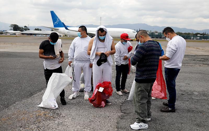Migrantes guatemaltecos esperan en la pista del Aeropuerto Internacional La Aurora en la Ciudad de Guatemala el 6 de enero de 2021, tras ser deportados de Estados Unidos. Un tribunal de apelaciones del circuito federal dijo el 8 de enero que una orden ejecutiva de la administración Trump que hubiese permitido a funcionarios de gobiernos estatales y locales rechazar a refugiados en su jurisdicción violaba prácticas de reasentamiento. (Foto CNS por Luis Echeverría/Reuters)