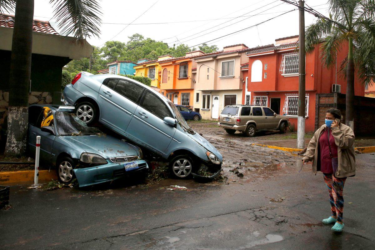 Una mujer con una mascara protectora pasa junto a autom—viles da–ados en San Salvador, El Salvador, el 31 de mayo de 2020, despues de que la tormenta tropical Amanda azotara el area.