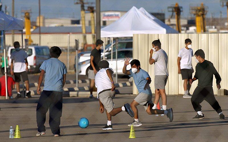 Niños migrantes no acompañados juegan al fútbol en una instalación de vivienda temporal en Midland, Texas, el 8 de abril de 2021. (Foto CNS por Paul Ratje/Reuters)