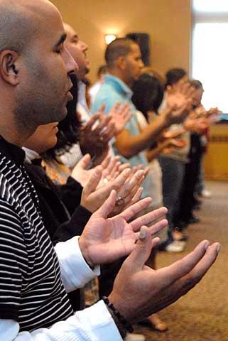 People raise their hands in prayer.