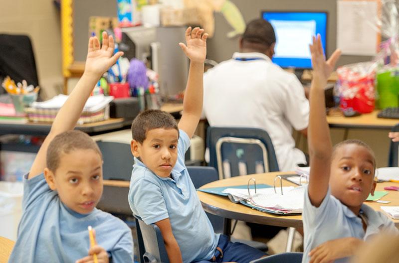 Los alumnos de tercer grado Ángel Sepúlveda-López (de izquierda a derecha), Freitty García y Esaiyu Joseph levantan sus manos durante la clase de matemáticas el 24 de junio de 2015, en la escuela chárter Eugenio María de Hostos en Rochester.