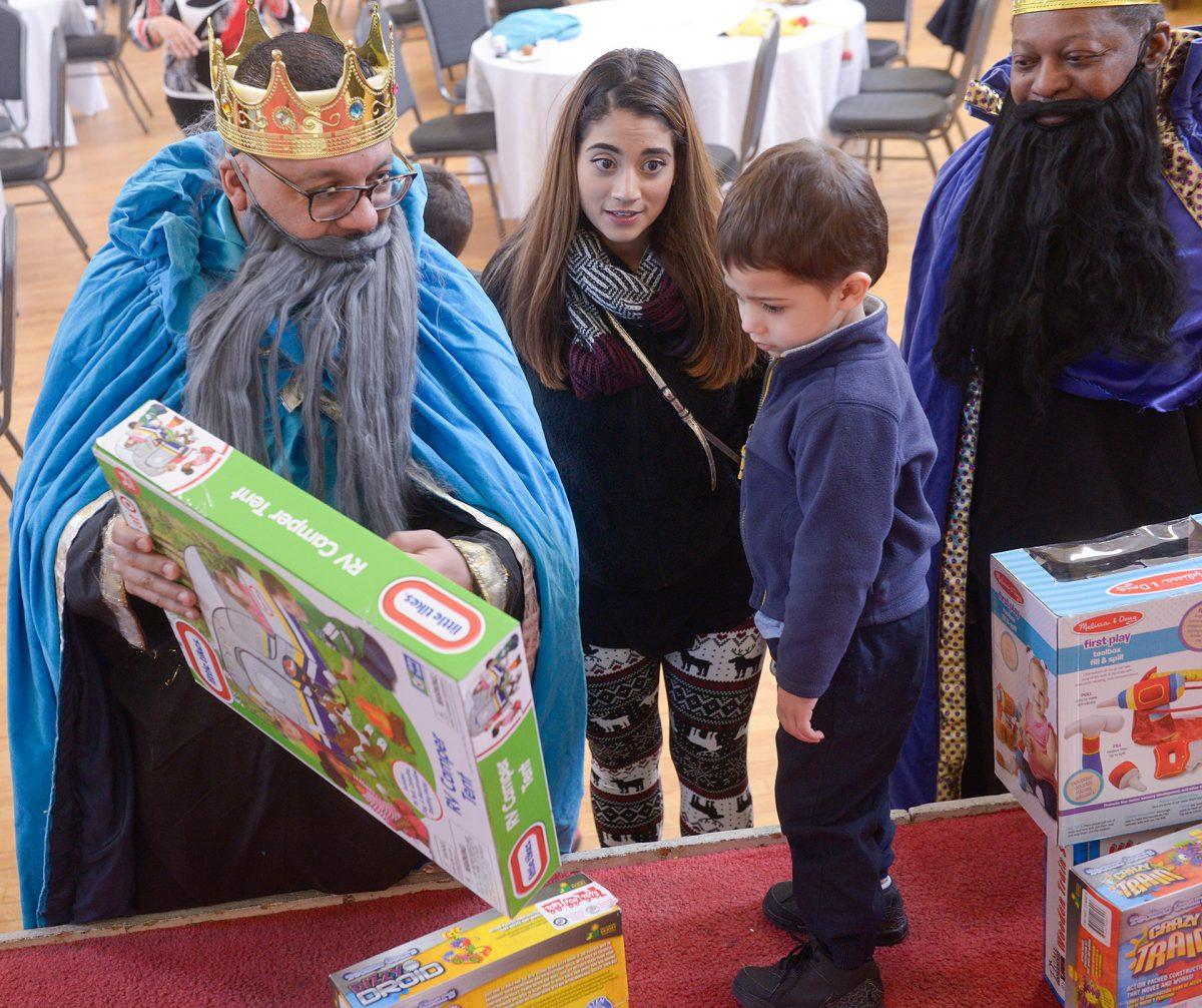 Cristal Santiago (centro) observa mientras Ray Mayoliz, representando a uno de los Reyes Magos, le da un regalo a Jovani Ortiz durante Nuestro Cultura, Nuestra Salud el 26 de enero en la Iglesia San Miguel en Rochester.