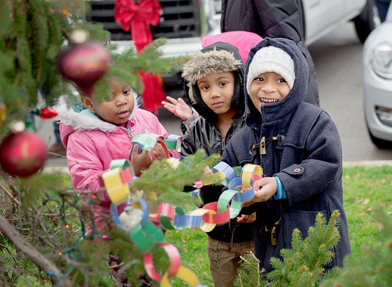 Kids decorate Christmas tree.