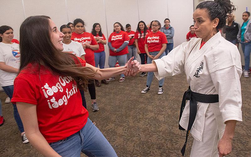 Jasmeliz Rivera (izquierda) practica con Mary Méndez Rizzo para liberarse del asimiento durante un taller de defensa personal que se ofrece en la reunión ¡Soy Única! ¡Soy Latina! en Roberts Wesleyan College el 18 de mayo.