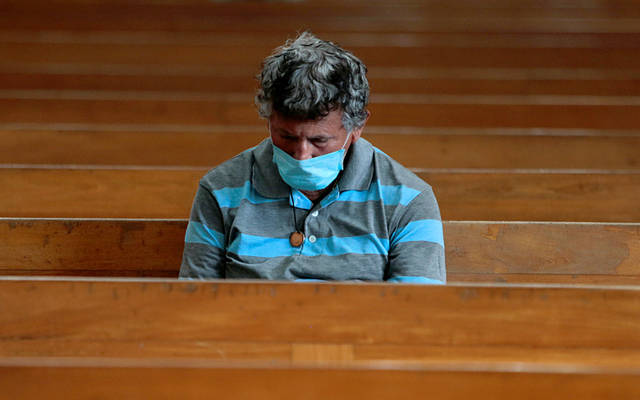 A man wearing a mask sits in a pew.