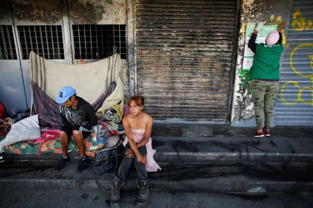 Un trabajador municipal coloca un cartel con información cerca de personas sin hogar en la Ciudad de México el 31 de marzo del 2020, durante la pandemia de COVID-19. (Foto CNS — Gustavo Graf, Reuters)