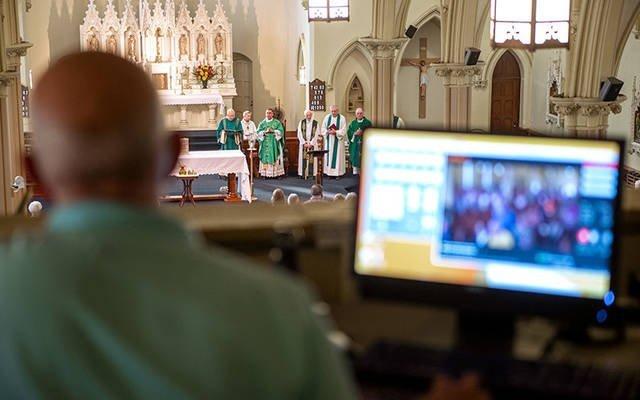 El operador de video Mike Paulin mira por encima de la cámara durante una Misa del 15 de septiembre de 2018 en la iglesia de Santa María en Corning. (Foto de archivo) El operador de video Mike Paulin mira por encima de la cámara durante una Misa del 15 de septiembre de 2018 en la iglesia de Santa María en Corning.
