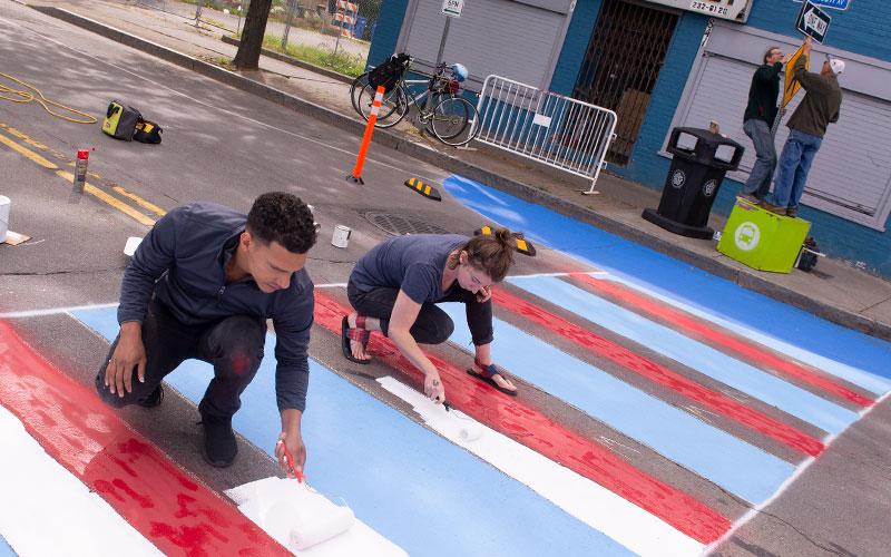 Santos Cruz y Anna Keller pintan un cruce de peatones mientras Scott Wagner y Frank Staropoli instalan un letrero de cruce de peatones en la Avenida North Clinton de Rochester el 29 de septiembre como parte del programa Complete Streets Makeover.