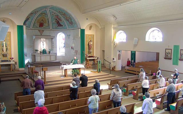 Se puede ver a los feligreses que asisten a Misa en la Iglesia de la Santísima Trinidad de Webster el 15 de junio manteniendo prácticas de distanciamiento social.