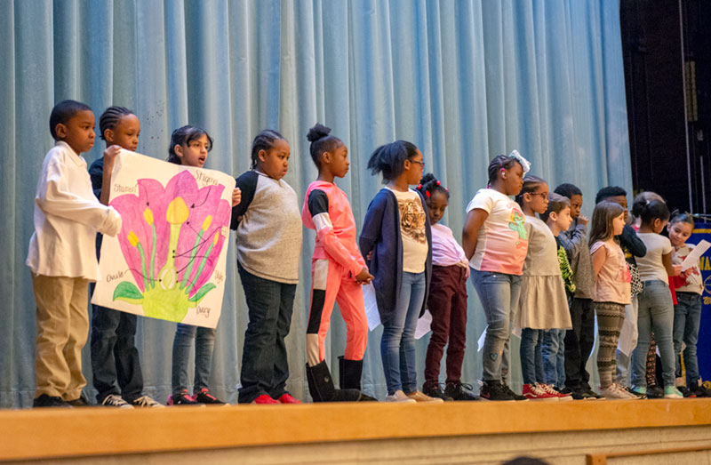 Durante una asemblea escolar el 5 de abril, unos estudiantes en la Escuela No 10, Dr. Walter Cooper Academy, presentan la anatomia de una flor.