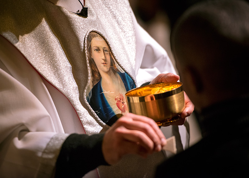 El Padre Anthony Mugavero distribuye la Comunión el 20 de enero en la Iglesia Nuestra Señora de las Américas durante la Misa anual celebrando a Nuestra Señora de Altagracia.