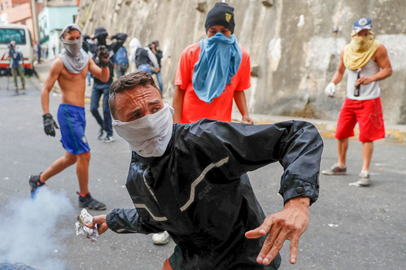 """A demonstrator throws back a tear gas canister while clashing with the Venezuelan National Guard Jan. 21, 2019, during a protest close to one of their outposts in Caracas. The Venezuelan bishops' conference labeled fresh calls for anti-government street protests as """"a sign of hope"""" in the country, which continues to suffer through a deep economic and humanitarian crisis. (CNS photo/Carlos Garcia Rawlins, Reuters) See VENEZUELA-BISHOPS-PROTESTS-SUPPORT Jan. 23, 2019."""