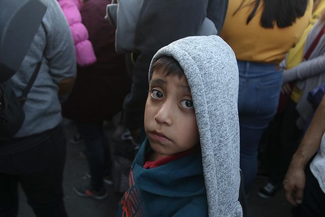 Un niño se encuentra entre personas en Juárez, México, que están a punto de rezar antes de cruzar el Puente Internacional Lerdo hacia El Paso, Texas, el 12 de octubre.