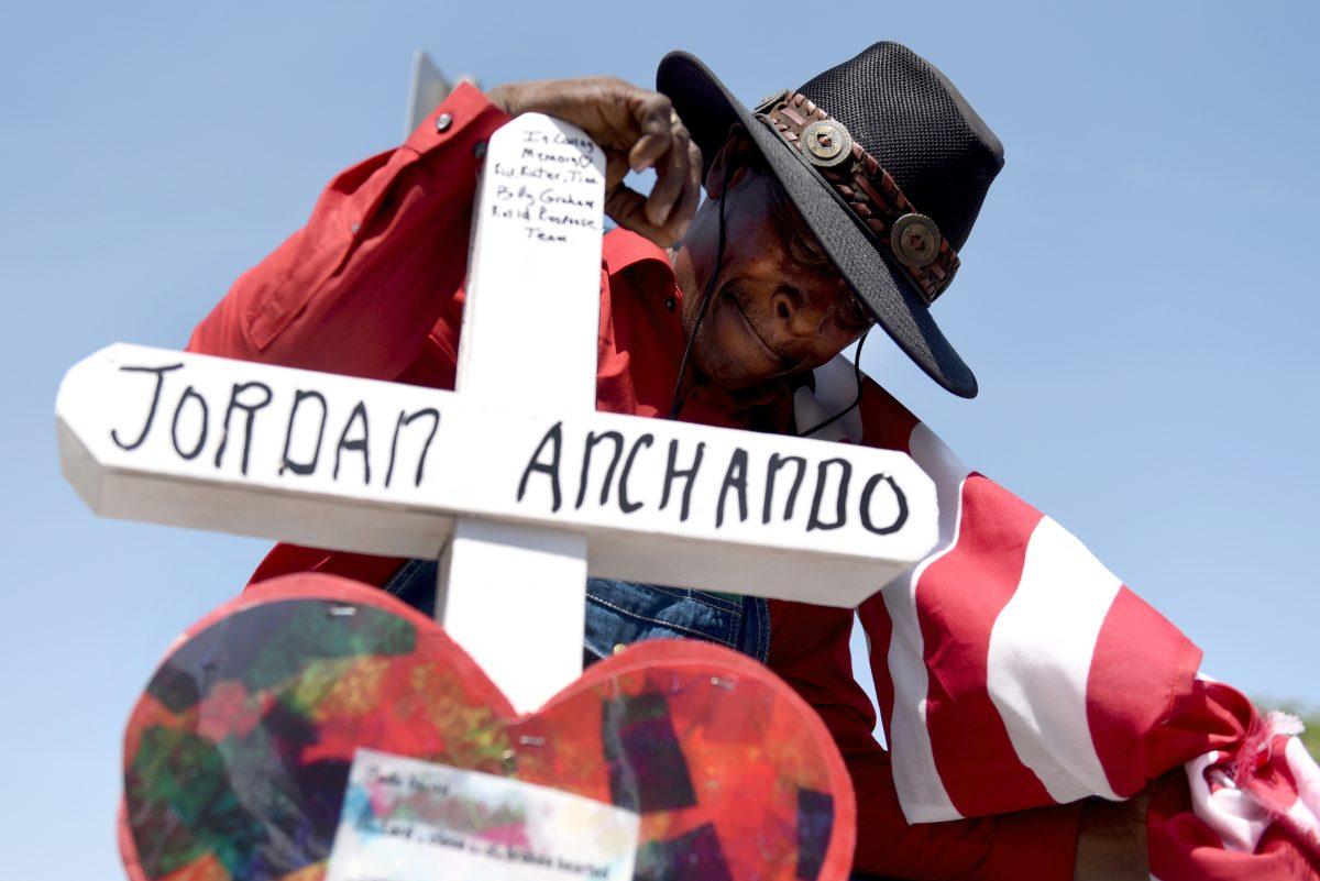 Curtis Reliford se arrodilla el 5 de agosto cerca una cruz colocada por Greg Zanis de Aurora, Ill., en honor de Jordan Anchando, una de las víctimas de un tiroteo masivo en una tienda Walmart en El Paso el 3 de agosto. Zanis ha creado más de 26,000 cruces de madera para los sitios de tragedias desde el 1996.