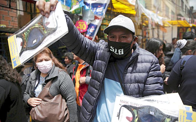 Un hombre sostieneUn hombre levanta mascarillas para la venta en la calle.