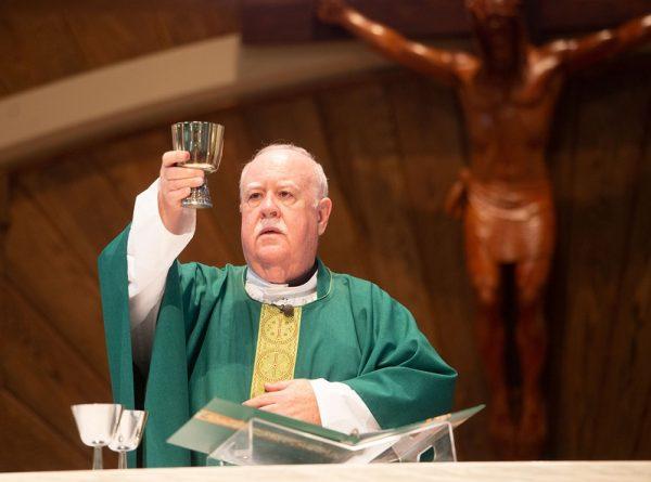 El Padre Joseph McCaffrey celebra la Eucharistía.Priest prepares for Communion