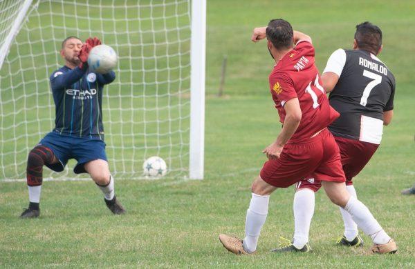 El porter bloquea un disparo durante un partido de fútbol.