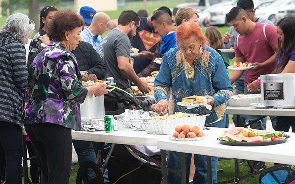 La gente se alinea para un picnic destacando comidas típicas latinoamericana y estadounidense.