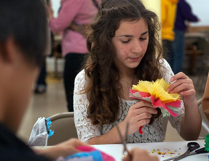 Katharina Nieves hacen una flor de papel picado y tubos de colores durante la celebración del Día de los Muertos.