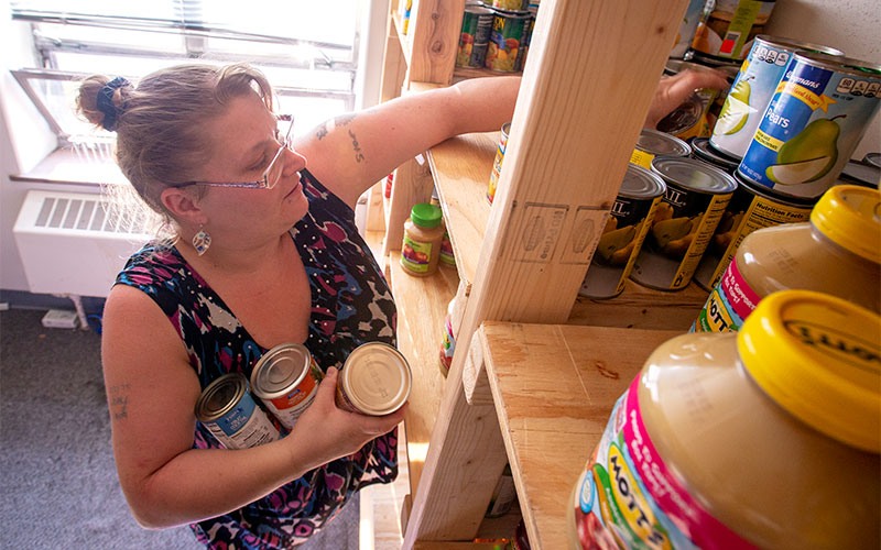 Woman pulls items from shelf.