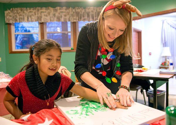 Heidi Franco-López (izquierda) y Emily Hanehan contribuyen a un impreso de un árbol de Navidad.