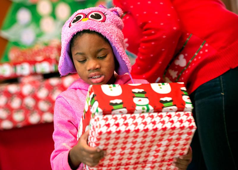 Taneisha Jackson lleva los regalos recibidos de Santa Claus durante la fiesta.