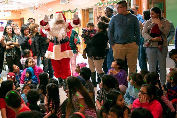 Santa Claus entra a la pista de baile para distribuir regalos a los niños presente.