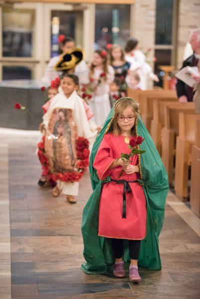 Emilia Nicolay-Carrera, de siete años, lidera una procesión de rosas antes de la presentación de los regalos durante una misa del 12 de diciembre celebrando a Nuestra Señora de Guadalupe en la Iglesia de San José en Penfield.