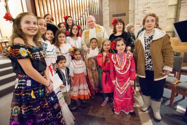 Niños participando el 12 de diciembre en la celebración de Nuestra Señora de Guadalupe en la Iglesia San José en Penfield posan con el Padre James Schwartz al final de la Misa.