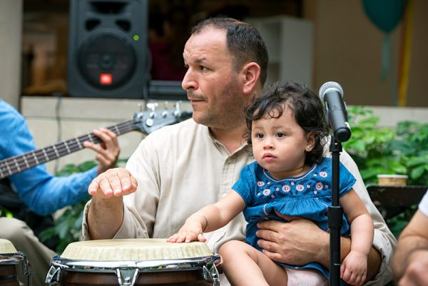Luca Santana plays with the Luca Santana Jazz Band while holding his daughter, 2-year-old Claire Santana, during the Memorial Art Gallery's Hispanic/Latino Heritage Family Day Oct. 8.