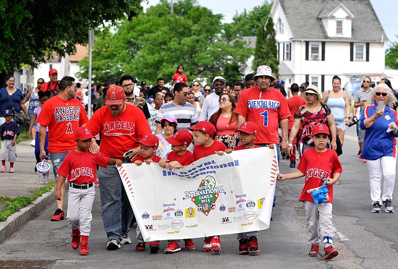 Jugadores, entrenadores y miembros de sus familias caminan hacia el parque de la Calle Baden el 4 de junio durante un desfile como parte de las ceremonias de apertura para la Liga de Béisbol Juvenil Hispana de Rochester.