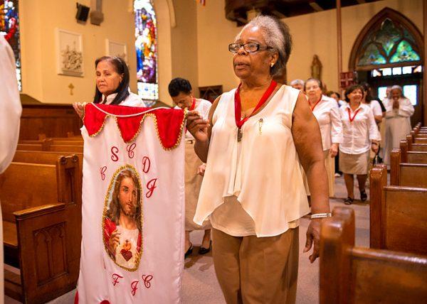 Antonia Hernández (izquierda) y Fanny DeJesús del grupo del Sagrado Corazón procesan en la Iglesia Santos Apóstoles en Rochester antes de la Misa el 23 de junio.