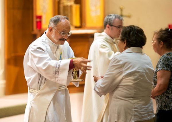 El Diácono Carlos Vargas distribuye la Eucaristía durante la Misa en honor de San Juan Bautista.